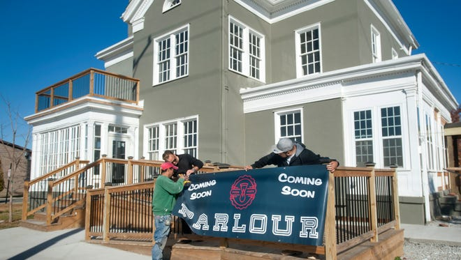 Sprigler's Construction workers Roberto Moran, left, and Victor Estrella, right, and construction company owner Chad Sprigler, center, hang a banner advertising the soon-to-open Parlour pizza restaurant located at the foot of the Big Four Bridge in Jeffersonville.