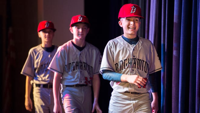Jude Abbadessa leads the way as members of Little League World Series champion Maine-Endwell help the Binghamton Rumble Ponies unveil their road uniforms during a ceremony at Maine-Endwell Middle School on Wednesday.