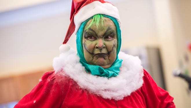 Pat Grant, 75, of Binghamton, performs as the Grinch during a skit with the Binghamton First Ward Senior Center Chorus on Tuesday.