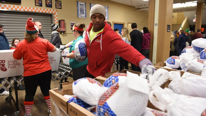 Dedrick Jackson helps to put turkeys in each Empty Stocking Fund basket as they are distributed  Friday, Dec. 23, 2016, at the Jacobs Building in Chilhowee Park. Over 3,500 baskets of food along with toys and books were distributed.