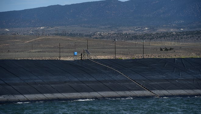 The dam for the treated waste water reservoir is seen at the Bently Ranch near Minden on Aug. 14, 2015. The ranch uses the water on crops not intended for human consumption.