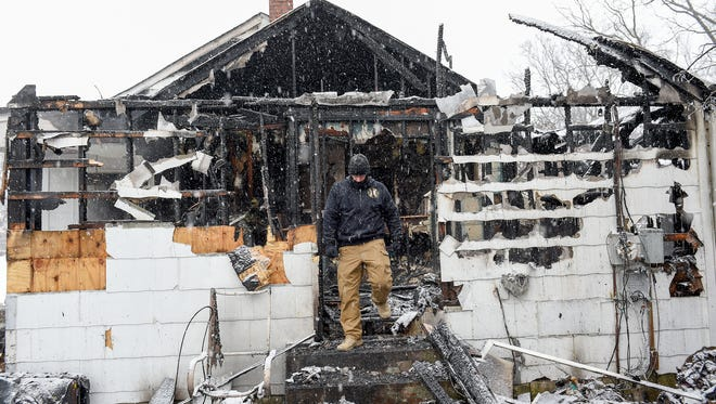 Nashville Fire Investigator Roy Watson walks through a home on Convair Circle destroyed by fire Friday Jan. 6, 2017, in Nashville, Tenn. The homeowners were safe but their two cats were killed.