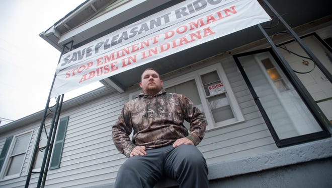 Josh Craven, the president of the Pleasant Ridge Neighborhood neighborhood association, in Charlestown, sits on his porch at 203 Guilford Road underneath a sign calling on the city to save their neighborhood by stopping what the neighborhood calls eminent domain abuse.11 January 2017