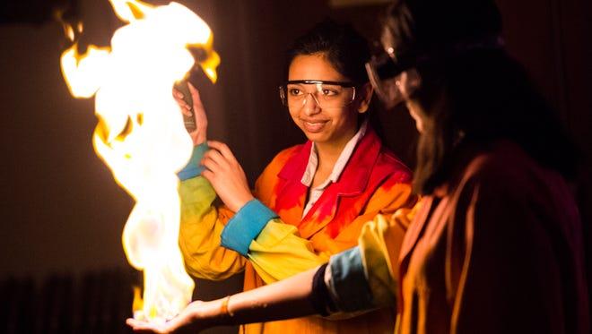 Vestal High School senior Anika Dalvie, 17, lights methane gas on a classmates hand during Wednesday's chemistry magic show put on for Glenwood Elementary fourth-graders.