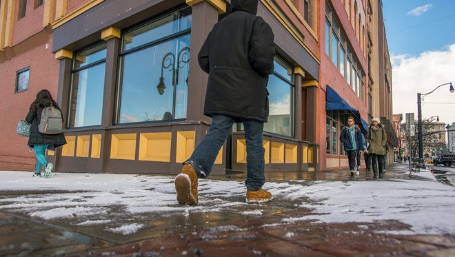 Pedestrians pass the empty storefront at 5 Court St., the former location of RiverRead Books.