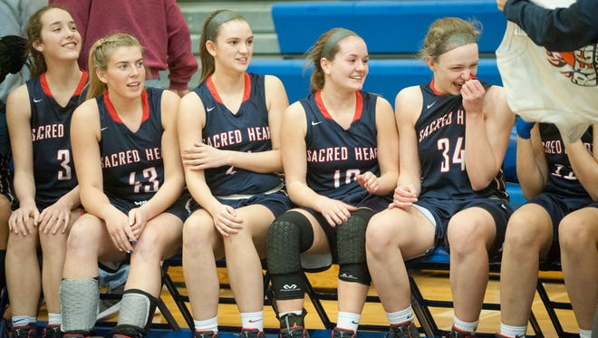 The Sacred Heart bench reacts as KHSAA 7th Region Girls Basketball Championship t-shirts are handed out following the team's win against Manual, 59-52.04 March 2017