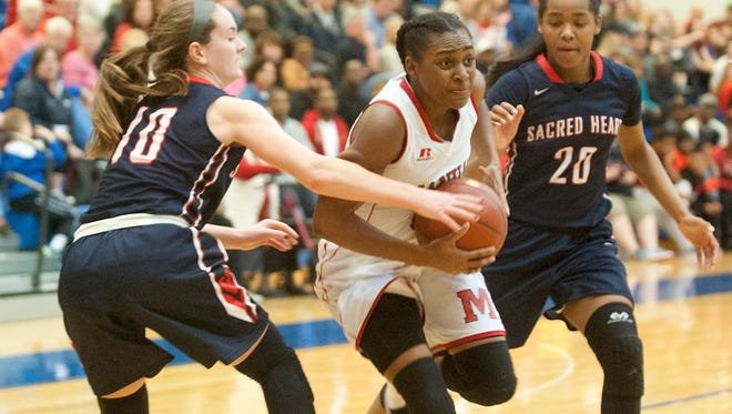 Sacred Heart guard Kieran Samsel, left, tries to steal the ball from Manual guard Jaela Johnson as Sacred Heart guard Kia Sivils applies pressure from the right in the KHSAA 7th Region Girls Basketball Championship. March 4, 2017