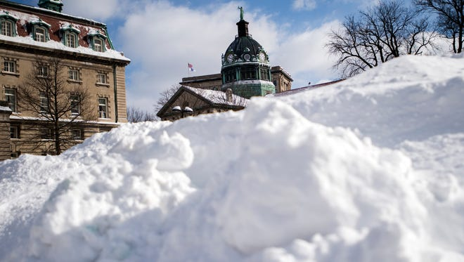 The Broome County Courthouse seen behind a pile of plowed snow during Snowstorm Stella in March 2017 in Binghamton.