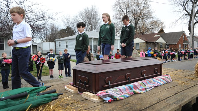 Photo by Alan Warren, Messenger-Inquirer/awarren@messenger-inquirer.comStudents walk by the casket of Most Rev. John Jeremiah McRaith on top of a farm wagon as it stops momentarily at Owensboro Catholic 4-6 Campus along East 22nd Street on Thursday during a procession through town to St. Stephen Cathedral.