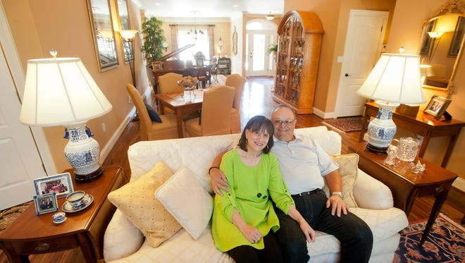 Debbie and Ken Hayes sit on their living room couch. Their Middletown home features 4,000 square feet of space.