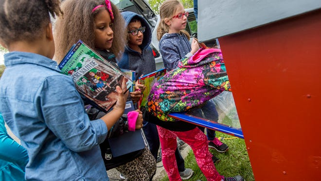 "Second-grade students from Vestal Hills Elementary place donated books into the new ""little library"" in front of Ted Brewster's home on Monday afternoon."