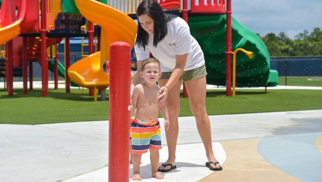 Davi Vincent putting sunscreen on her son Reece before playing in the water in the splash pad at St. Julien Park- Saturday, July 8, 2017.