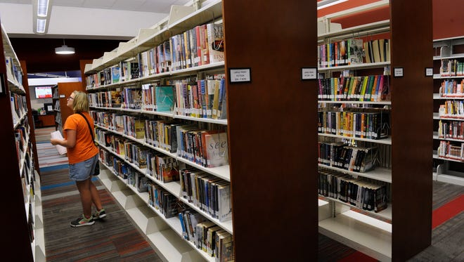 Rylee Stevens searches for a book at the South Branch of the Abilene Public Library. The library, which opened last year, is located in the Mall of Abilene in a space formerly occupied by a Zumba studio and an Old Navy store before that.