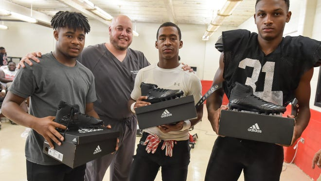 Dr. Brent Rochon, second from left, donates more than 40 pairs of cleats to Northside High football players Tuesday, Aug. 15, 2017.