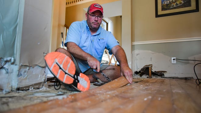 Friendswood, Texas resident Donnie Guillory removes wood floors to begin the cleanup process after rising flood water from Tropical Storm Harvey inundated his home. He estimates that his home suffered up to $100,000 of damage in the flooding.