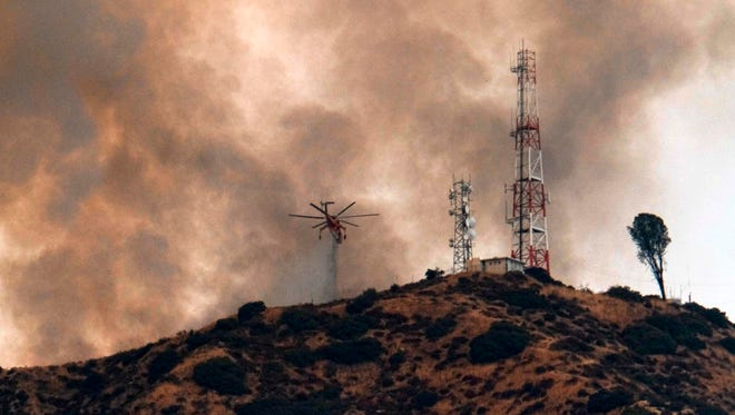 A helicopter makes a water drop amid black smoke rising from a wildfire burning in the Tujunga area of Los Angeles, seen from nearby Burbank, on Friday afternoon.
