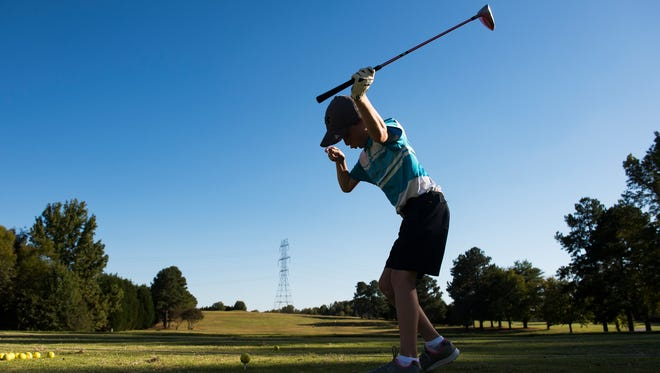Jackson Merriss, 8, swings his club on the driving range at the Smithfields Country Club on Wednesday, Oct. 5, 2017. Meriss, who has cerebral palsy, swings using only his left arm. He took up interest in the sport at an early age and now plays nearly every day with his father Todd and twin brother Caden.