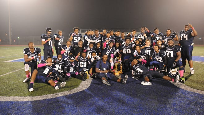 Thurston High School's football team pose with the Supervisors Cup trophy after a come from behind win against Redford Union with a final score of 42 - 40 in overtime.