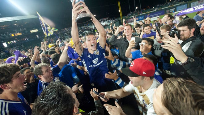 Louisville City FC defender Kyle Smith holds up the USL Eastern Championship trophy after defeating New York Red Bulls in penalty kicks after the teams remained tied in regulation and overtime