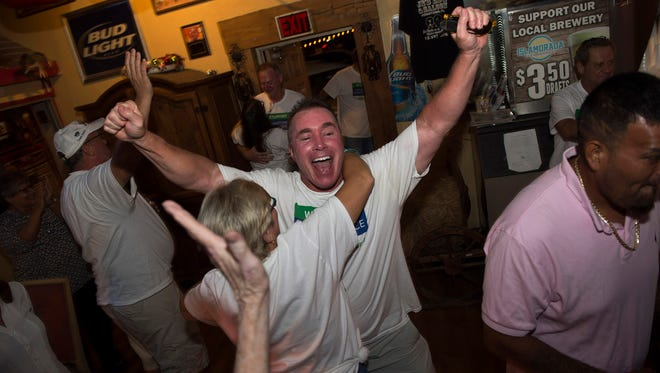 Scott Watson, of Indiantown, (center) receives a hug from Ande Bauzenberger, of Indiantown, (left) as he celebrates with members of the Indiantown Independence Group after Indiantown's incorporation vote passed, at JR's BBQ and Saloon on Nov. 7, 2017, in Indiantown.