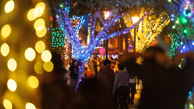 Families walk around the many glittering trees at the Glendale Glitters Spectacular Weekend on Friday, Nov. 24, 2017, at Murphy Park in downtown Glendale, Ariz.