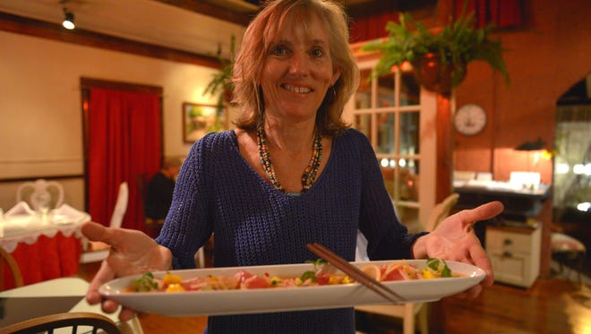 Margie Perrin shows off a dish made by her husband, Michael, in 2014 at 11 Maple Street in Jensen Beach.