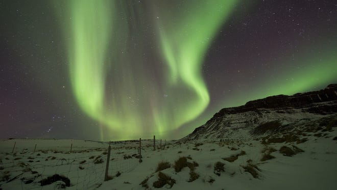 The Northern Lights, or aurora borealis, appear in the sky over Bifrost, Western Iceland on March 1, 2017. The Northern Lights are created as a result of collisions between gaseous particles in the Earth's atmosphere and charged particles released by the sun, according to the Northern Lights Space and Science Centre in Canada.