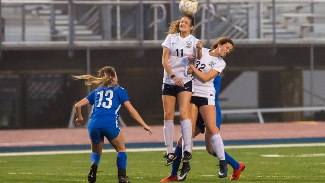 STM's Emily Champion converts a header during the Lady Cougars' loss to St. Scholastica on Wednesday.