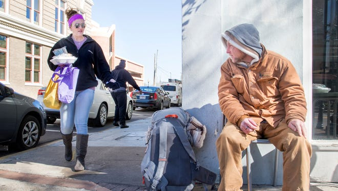 Angi Orlik, of Silverhill, Alabama, approaches John Elmalih with some hot food and warm clothing on a freezing day in downtown Pensacola on Wednesday, January 17, 2018.  Orlik and her girlfriend Arnetra Dale have been collecting and distributing necessities to homeless in Pensacola and Mobile every Wednesday for the past year.