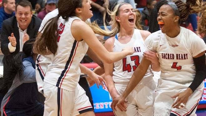 L-R: Sacred Heart center-forward Kristen Clemons, Sacred Heart guard Natalie Fichter and Sacred Heart forward Cierra Scott celebrate their 83-48 victory over Mercer County in the 46th annual Girls Louisville Invitational Tournament championship game.