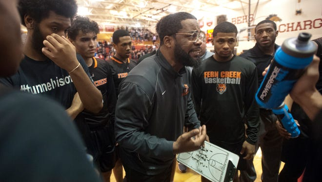 Fern Creek head basketball coach James Schooler, III talks to his players during a time-out.
