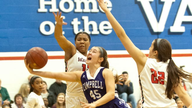 Campbell County guard Lexie Stapleton puts up a shot between Sacred Heart guard Erin Toller, left, and Sacred Heart center-forward Kristen Clemons, right.Feb. 02, 2018