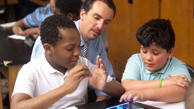Frederick Law Olmsted Academy North Middle School Principal Ryan Rodosky, center, listens as 6th grade science students Matthew Jaques, 12, left, and Aiden Hoyalnd, 11, demonstrate a computer-generated simulation of atoms when heating up.April 25, 2018