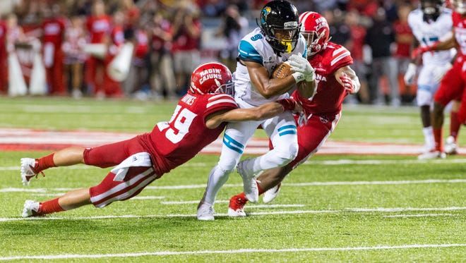UL defenders converge on Coastal Carolina wide receiver Malcolm Williams during the Cajuns' 30-28 home loss to the Chanticleers on Saturday at Cajun Field.