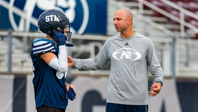 St. Thomas More wide receivers coach Lance Strother talks strategy with one of his Cougar receivers during a practice session in preparation for the Division II state finals game at 3:30 p.m. Friday against No. 1 University.