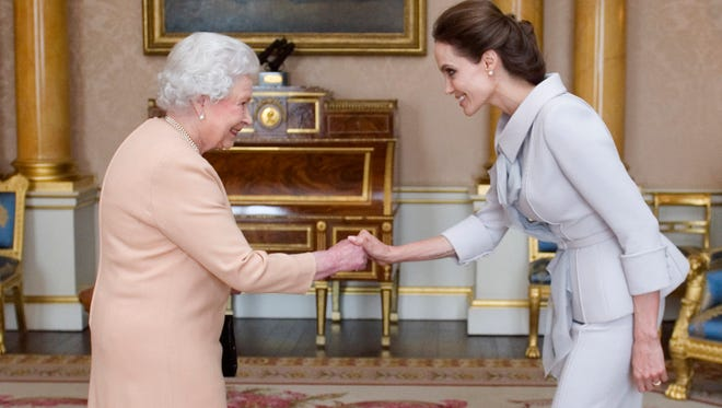 Actress Angelina Jolie is presented with the Insignia of an Honorary Dame Grand Cross of the Most Distinguished Order of St Michael and St George by Queen Elizabeth II in the 1844 Room on October 10, 2014 at Buckingham Palace, London.