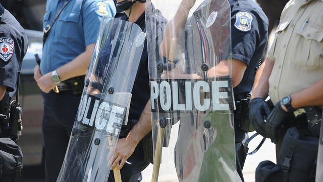 Police officers equipped in riot gear line up during a protest of the shooting death of 18-year-old Michael Brown outside Ferguson, Mo., Police Department headquarters Aug. 11.