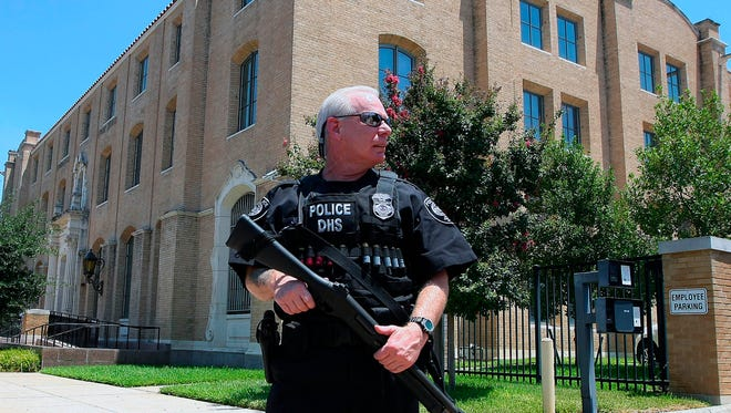 A Department of Homeland Security officer stands guard outside the federal court building, Thursday, Aug. 4, 2011, in Waco, Texas.