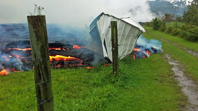 This Oct. 25, 2014, photo provided by the U.S. Geological Survey shows a small shed being consumed by lava near the town of Pahoa on the Big Island of Hawaii.