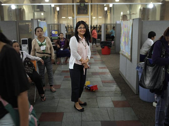 Hkadin Lee stands in the center of a busy St Mary's Place refugee center where she is a services coordinator. Lee came to this country from Burma in 1990 and shared her story with StoryCorps.