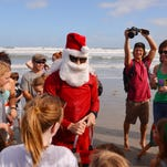 At 2:00 p.m. Friday after noon, Surfing Santa arrived at Shepard Park in Cocoa Beach, surfing in on eight foot waves with hundreds onshore cheering him on.
