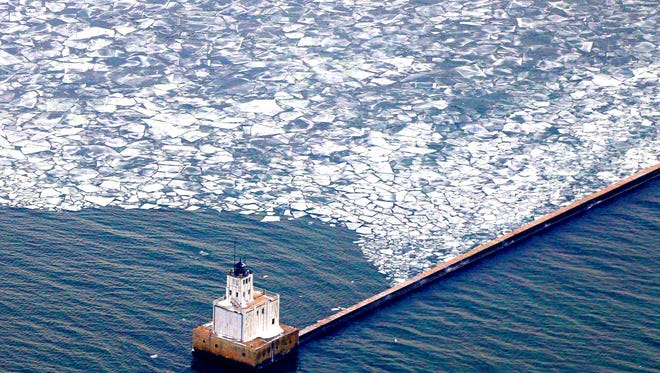 An aerial photograph of the breakwater lighthouse in Lake Michigan in December.