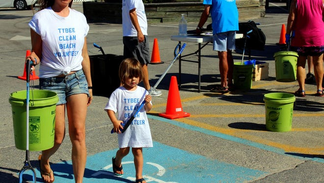 Danielle Wiltie and her son Asher march to the beach with their litter-picking equipment.