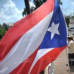 A Puerto Rican flag waves in the wind while speakers talk during the Puerto Rican flag raising ceremony at Vineland City Hall, Sunday, Jul. 19, 2015.  Staff Photo/Sean M. Fitzgerald