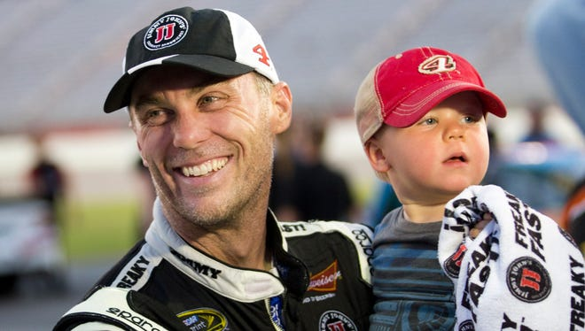 Sprint Cup Series driver Kevin Harvick (4) holds his 2-year-old son Keelan after winning the pole for the Oral-B USA 500 at Atlanta Motor Speedway on Friday.