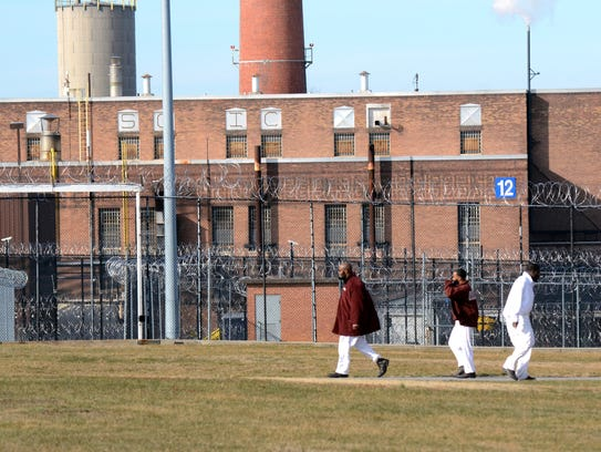 Inmates walk across a yard at the State Correctional