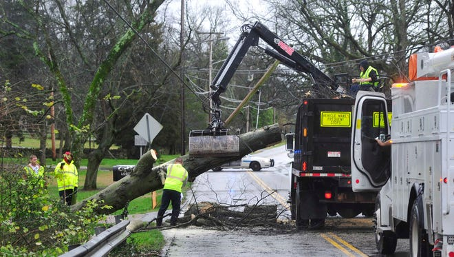 Metro Public Works employees remove a tree that fell across Granny White Pike just south of Harding Place Monday afternoon, Dec. 28, 2015 in Nashville, Tenn.