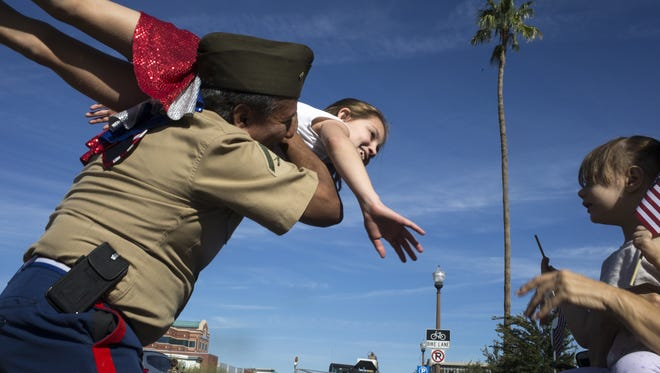 Henry Carrejo and 9-year-old Kylie Clinton, both Arizona Swing Kids, greet spectators during Tempe's Veterans Day Parade on Nov. 10, 2017.