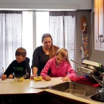Nicole Rich, 34, helps her children Jamison, 7, left, and Jersey, 9, do their homework in Ithaca, N.Y. The siblings attend Caroline Elementary School in the Ithaca City School District, where water samples recently came back with high lead results.