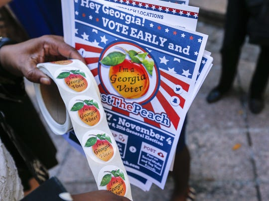 An election official hands out stickers to encourage early voting in Atlanta on Oct. 17, 2016.